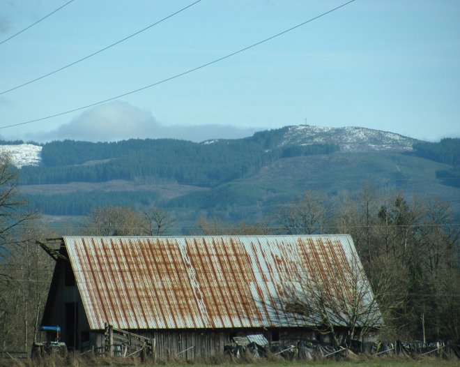 Old barn with mountains in the background.